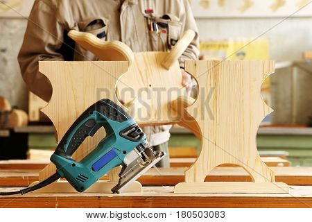 Woodwork with electric jigsaw in a carpentry