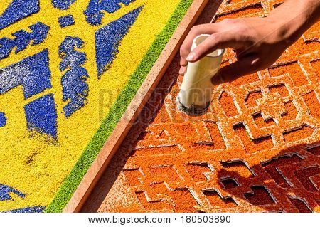 Antigua, Guatemala - March 26 2017: Local decorates Lent carpet for procession using stencil & dyed sawdust in colonial town with most famous Holy Week celebrations in Latin America.