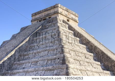 Famous El Castillo pyramid with shadow of serpent at Maya archeaological site of Chichen Itza in Yucatan Mexico under sunny blue sky