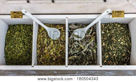 White wooden box with dried herbs and two white tea spoons
