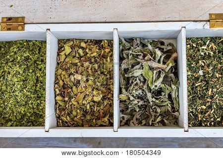 White wooden box of tea with dried tea herbs
