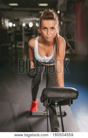 Beautiful young muscular woman doing exercise to strengthen her back at the gym. Looking at camera.