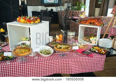 table in the restaurant served for brunch. roasted pig, spinach pie, pie with salmon, sliced meat, cheese plate, sliced fresh vegetables. cutlery