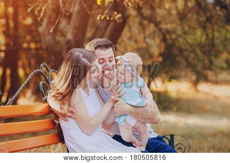 mom dad and little daughter sitting on a bench in the sunny park