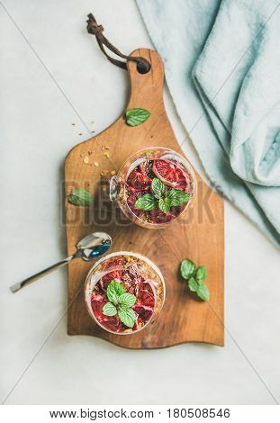Healthy breakfast. Greek yogurt, granola, blood orange layered parfait in glasses with fresh mint on rustic wooden board over grey marble background, top view. Clean eating, weight loss food concept