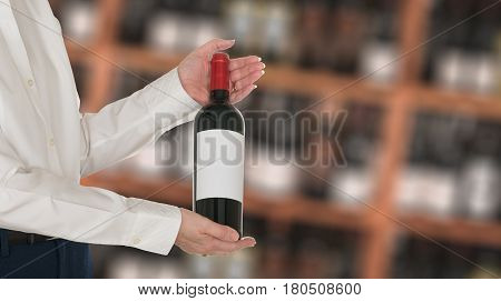 Senior female caucasian wine steward offering a bottle of red wine with blank label to a customer in a wine store or winery. The bottle is ready with copy space.