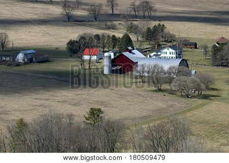 A farm and old farmhouse surrounded by stone wall fences.