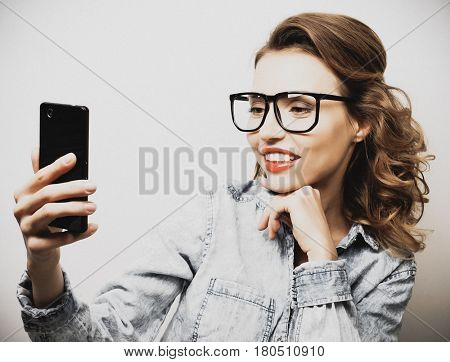 Taking picture. Smiling cheerful blond-haired woman doing selfie