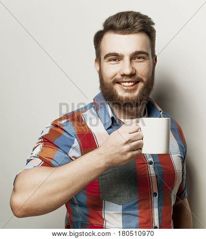 young bearded man with a cup of coffee against grey background