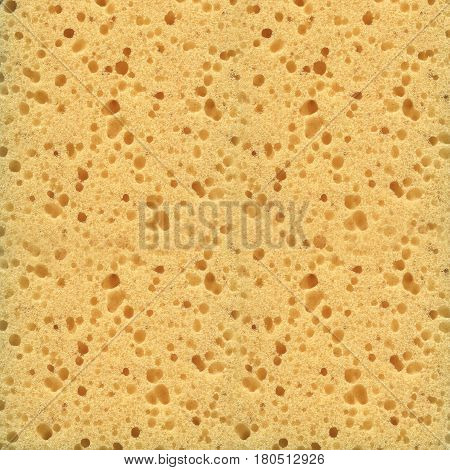 Yellow sponge close-up texture. Abstract background of a porous material.