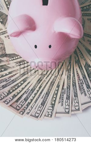 Piggy bank style money box on background with money american hundred dollar bills.