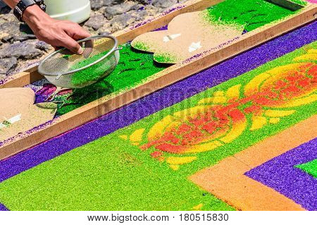 Antigua, Guatemala - March 26 2017: Local sifts dyed sawdust through stencil to decorate Lent carpet for procession in colonial town with most famous Holy Week celebrations in Latin America.