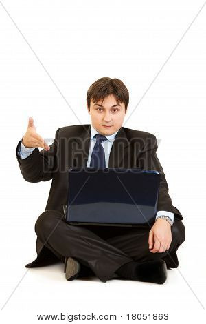 Sitting on floor with laptop surprised businessman pointing on laptops monitor isolated on white