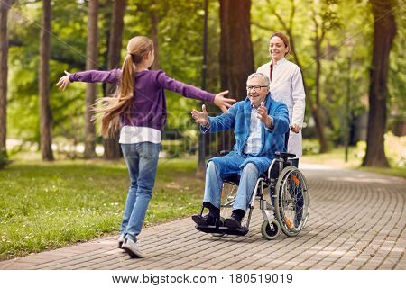 cheerful grandchildren visiting senior disabled father in park