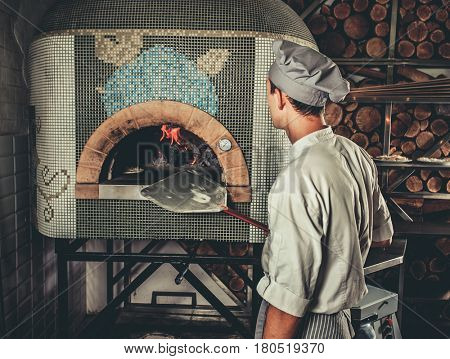 Food concept. Preparing traditional italian pizza. Young chef in white uniform holds in his hands shovel for pizza, he bakes dough in a professional oven in interior of modern restaurant kitchen