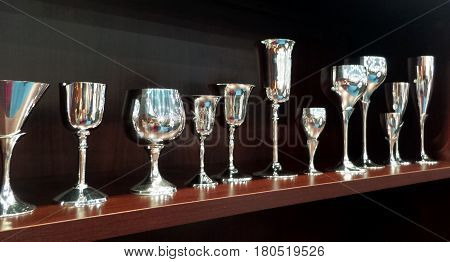 Row of silver drinking goblets on shelf.