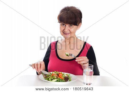 Pension age good looking smiling woman eating green salad