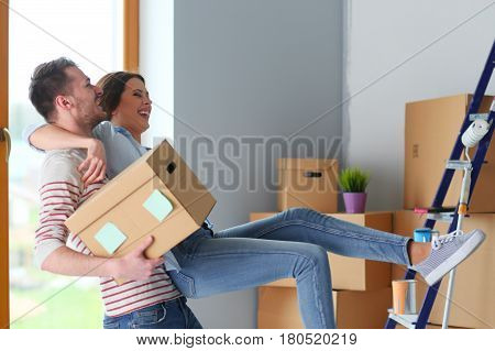 Happy young couple unpacking or packing boxes and moving into a new home.