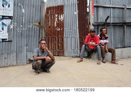 TEBING TINGGI NORTH SUMATRA INDONESIA - DECEMBER 18 2016: Three men sitting near fence at poor district of city.