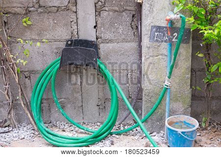 Green garden water hose hanging on brick wall connected to water tap.
