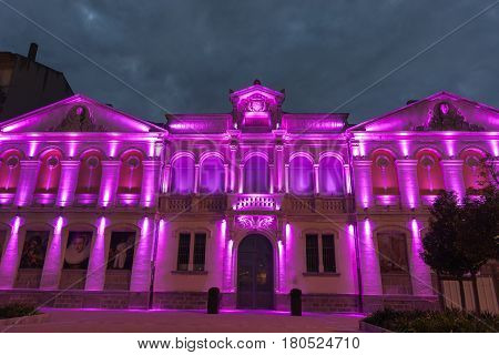 Carcassonne, France - October 20, 2016; Library of Design School building at night in purple light against dark cloudy sky Carcassonne France.