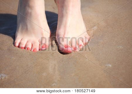 nice legs in water nice pedicure red nail sand beach