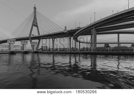 Black and White Suspension bridge connect to highway over watergate