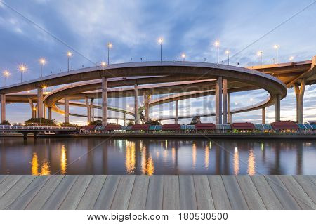 Opening wooden floor Overpass highway intersection river front night view with reflection