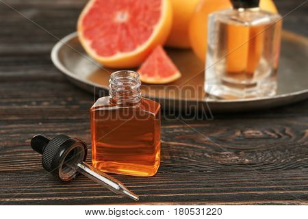 Bottle of perfume oil and metal tray with citrus fruit on wooden background