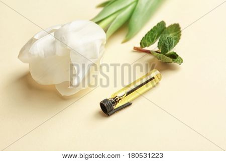 Beautiful composition with perfume sample, tulip and mint on color background