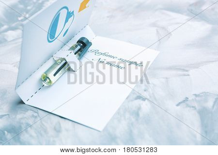 Perfume sample in paper cover on light background