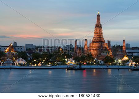 Wat Arun temple along with Bangkok river Thailand Landmark after sunset background