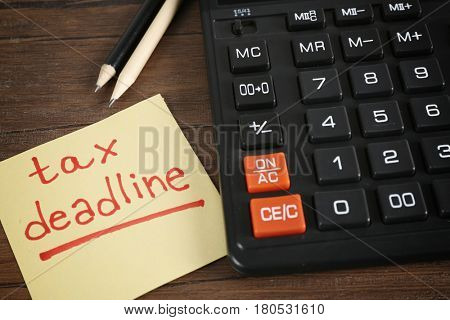 Paper sheet with text TAX DEADLINE, calculator and pencils on wooden table