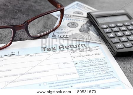 Tax return form, glasses, calculator and dollars on table