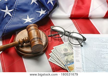 Judge gavel, eyeglasses, money and tax forms on American flag background