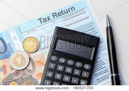 Tax return form, calculator, pen and money on table