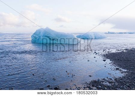 Ice cube breaking fron glacier on black small rock beach natural winter landscape background