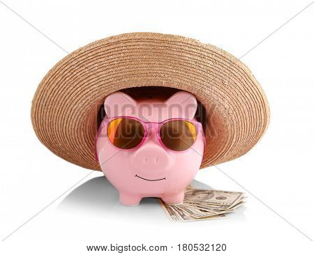 Vacation budget concept. Piggy bank in straw hat with sunglasses and money on white background