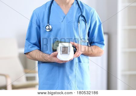 Young medical assistant with sphygmomanometer in office