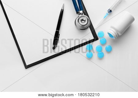 Cough drops, clipboard and medical equipment on white background