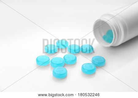 Cough drops spilling out of bottle on white background