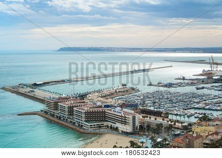 ALICANTE SPAIN - FEBRUARY 12 2016: A view from Santa Barbara Castle to a port of the city with a plenty of yachts to roofs of the buildings and to Mediterranean sea on cloudy day Alicante Spain.