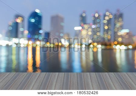 Opening wooden floor City office building blurred bokeh light at twilight water front abstract background
