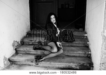Young Goth Girl On Black Leather Skirt, Jacket And Punk Shoes Sitting On Stairs Of Old House And Lis