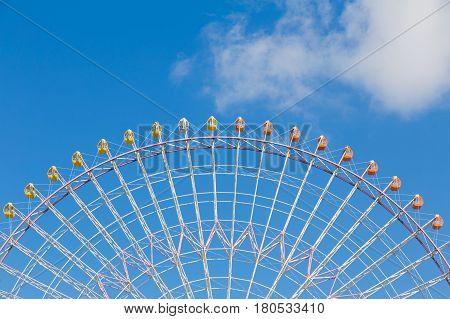 Path of big ferris funfair wheel with blue sky background