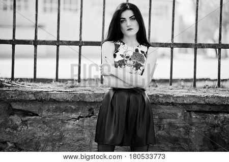 Young Goth Girl On Black Leather Skirt Against Iron Fence.