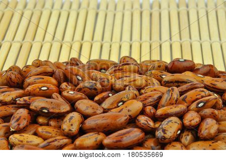 Brown pinto beans on bamboo mat, close up ripe legumes