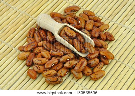 Brown pinto beans with wooden scoop on bamboo mat