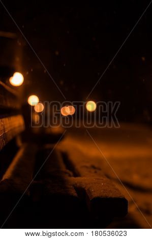 View of bench and shining lantern through snowing
