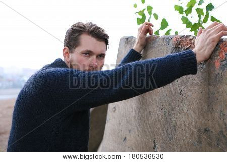 Bearded man in sweater leant on the wall.